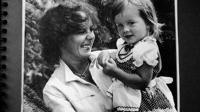 Ett svartvitt fotografi på Pirkko Mannola med sin dotter Heidi. Heidi småler in i kameran medan hon sitter i famnen på Pirkko som skrattar åt något.