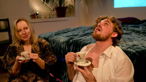 Milla Kangas (Sarah) ja Lauri Tilkanen (Richard) istuvat sängyn vieressä lattialla hiukset pörrössä ja juovat teetä.