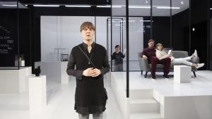 Eero Ritalan näyttelemä nainen seisoo kuvan etualalla huolestuneen näköisenä. Lavastus on kliinisen valkoinen ja hohtavan puhdas. Taustalla Naisen sisko (Lotta Kaihua), puoliso (Tommi Korpela) ja poika (Laura Rämä).