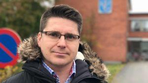Porträttbild av Vörås kommundirektör Mikko Ollikainen. Bilden är tagen utanför Vörå kommungård med ett kort skärpedjup.
