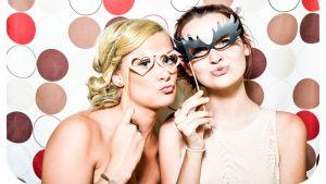 Kaksi tyttöä poseeraa juhlamaskit kasvoillaan.