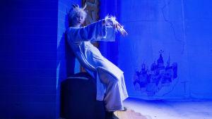 Herra Hakkarainen (tanssija Ninu Lindfors) nuokkuu seisten seinää vasten.