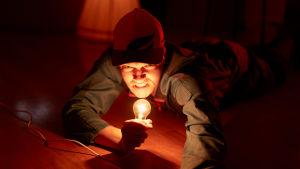 Näyttelijä Juho Uusitalo makaa lattialla ja pitää hehkulamppua kädessään kuin mikrofonia. Hänellä on työhaalari ja lippis.