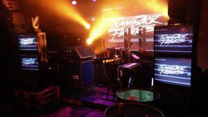 En scen på en av flashback future festerna. Många crt skärmar och synthar på scenen.