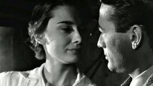 Audrey Hepburn ja Gregory Peck katsovat toisiaan lähikuvassa. Kuva elokuvasta Loma Roomassa.