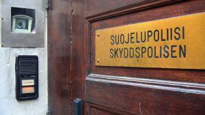 Skylt på skyddspolisens dörr där det står: Suojelupoliisi - skyddspolisen.