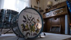 Till vänster ett trumset med bilder på djur och texten Burning Hearts och till vänster en tramporgel.