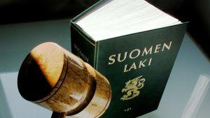 En grön bok med texten Suomen laki och ändan av en klubba i materialet trä.