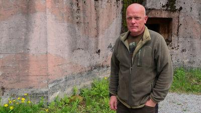 Porträtt på Jörgen Engroos. Bunkern Irma i bakgrunden.