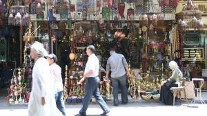 Ihmisiä kulkee basaarissa lamppu- ja vesipiippukaupan ohi.
