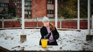 Katja Küttner istuu lumen peittämällä hiekkalaatikolla ja suuntaa mikrofoninsa leluämpäriin.