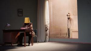 Elina Knihtilän näyttelemä mies istuu työpöydän ääressä hiljaa, ämpäri päässään.
