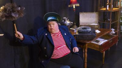 En skådespelare klädd som museivakt viftar med en dammvippa.