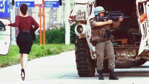 En kvinna i höga klackar springer över Sniper Alley medan en fransk fredsbevarare försöker skydda henne.