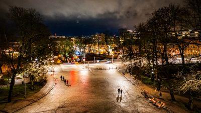 Några människor går över ett torg på kvällen. Det är inga löv på träden men ingen snö på marken.
