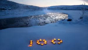 Talvinen jokimaisema, jossa kynttilöistä tehty numero 100.