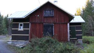 En gammal röd stuga som renoveras.