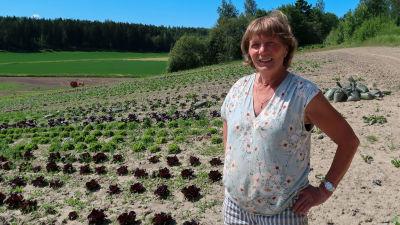 Porträtt av Ingrid Träskman som står vid sin grönsaksodling.