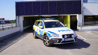En svensk polisbil som kör i ett parkeringshus