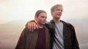 Þór och Kristján står och håller armarna om varandra med bergen och himlen som bakgrund.