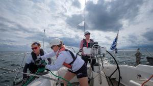 Tre kvinnor på en segelbåt ute till havs. En står vid rodret och två manövrerar segel.