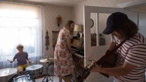Ett barn och två vuxna spelar musik tillsammans, trummor, tramporgel och gitarr.