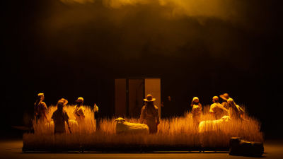 Kansallisteatterin näyttämöllä on vehnäpelto. Korsien lomassa seisoo ihmishahmoja lampaita. Ihmiset ovat selin kameraan. Tausta on musta ja pelto hahmoineen hohtaa kullankeltaista valoa.