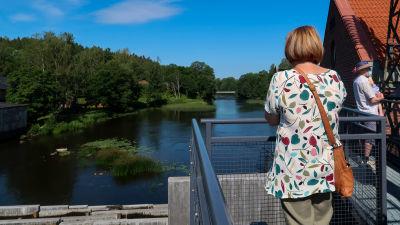 Kvinna som blickar ut över Svartån från en bro i Billnäs.