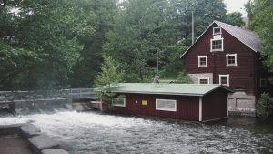 Två röda byggnader intill forsande vatten.