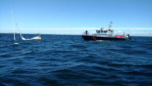 En segelbåt som håller på att sjunka och ett sjöbevakningsfartyg bredvid.