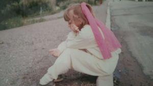 Mirka Saarela lapsena istuu tien poskessa