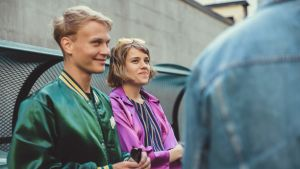 Elias Salonen ja Anna Airola hymyilevät farkkutakkiselle henkilölle.