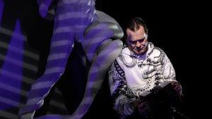 Tommi Liski näyttelee käärmettä. Kuvassa käärme nojailee pimeydessä veistokseen, jossa käärme kietoutuu miehen ympärille.