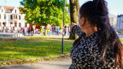 Kaisa Augusta Hansén-Suckow pekar på demonstranter i en park.