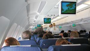 Passagerare och två flygvärdinnor inne i ett flygplan.
