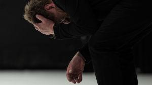 Timo Torikan näyttelemä mies painaa ahdistuneena päätään käsiinsä, puolikyykistyneessä asennossa.