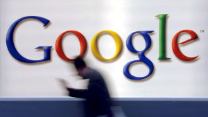 Man med mobil passerar en stor Google-logotyp.