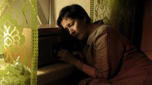 Wanda Dubielin näyttelemä Aliide Truu on polvistuneena vuoteellaan, pää vanhaa putkiradiota vasten painautuneena.