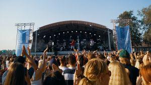Publikhav framför utomhusscen en varm sommardag. Många klappar och viftar med händerna.
