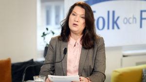 Ann Linde håller tal på rikskonferensen Folk och försvar vars logo syns i bakgrunden.