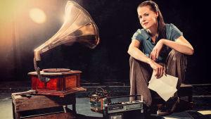 En kvinna vid en grammofonspelare.