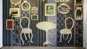 Salong +3 taiteilijaryhmän sinisävyinen vihanneksia ja sorkkia sisältävä installatio seinälle kiinnitettynä.