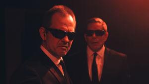 Robin Svartström ja Taisto Oksanen näyttelevät mustapukuisia miehiä Ryhmäteatterin Muodonmuutoksessa.