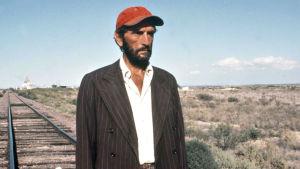 Harry Dean Stanton seisoo erämaassa raiteilla elokuvassa Paris Texas.