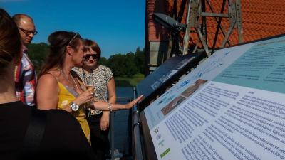 Bild av två kvinnor som läser information från en skylt.