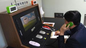 """En sydkoreansk regeringstjänsteman kommunicerar med en nordkoreansk kollega över den """"heta linjen"""" i gränsstaden Panmunjom den 3 januari."""