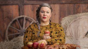 En kvinna med ett äpple mellan händerna.