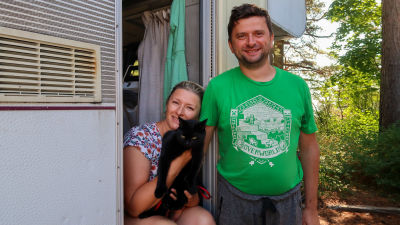 Porträtt av Irina och Vladimir Rogojin som står i dörren till deras husbil. Irina har en katt i famnen.