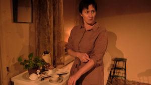 Wanda Dubielin näyttelemä Aliide Truu seisoo jääkaapin edessä vakavana ja käärii hihojaan.