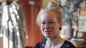 Vit kvinna med silverfärgade glasögon och det ljusa håret i en knut på huvudet ler mot kameran.